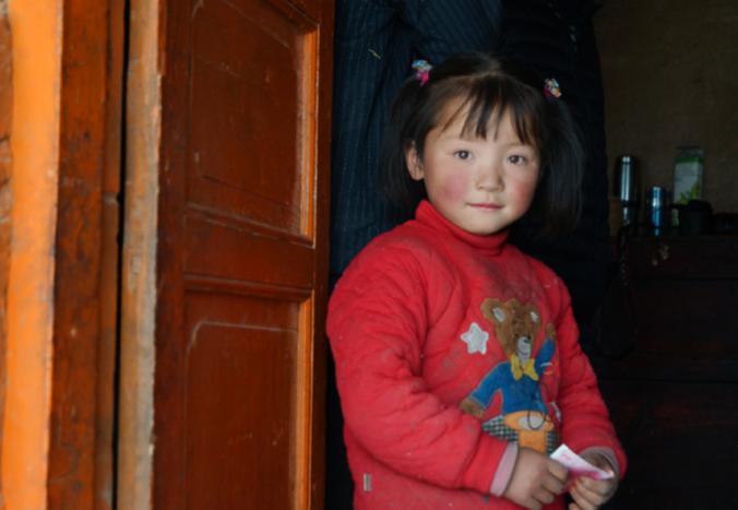 2016年4月25日,中国禁毒网记者走访青海省禁毒总队定向扶贫村时遇到这个5岁的小姑娘,母亲生下她便杳无音讯,父亲打工外出数年未归只得与75岁的爷爷以及40多岁瘫痪在床的姑姑相依为命。至今,村外的风景一无所知,学校的模样不曾见过。她明亮的眼睛,略带羞涩的稚嫩,天真可爱的笑脸,正是无忧无虑的年华。